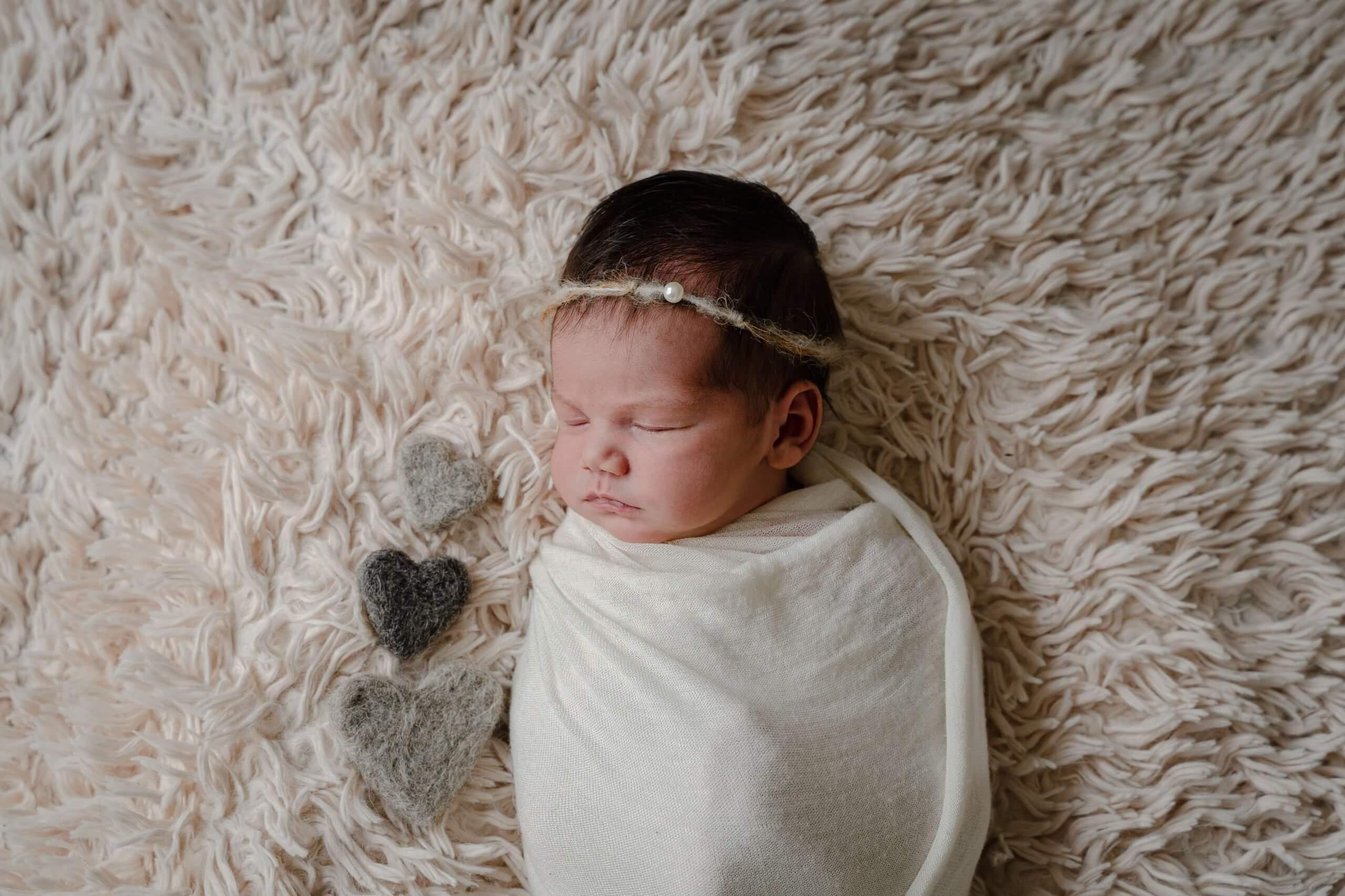 Newborn baby meisje slapen knuffel natuurlijk tinten lief bij je thuis